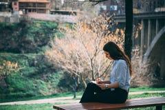 Κορίτσι που μελετά σε ένα πάρκο στοκ εικόνες