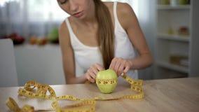 Κορίτσι που μετρά το μήλο με τη γραμμή ταινιών, που μετρά τις θερμίδες, τη οργανική τροφή και τη διατροφή στοκ εικόνα με δικαίωμα ελεύθερης χρήσης
