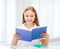 Κορίτσι που μελετά και που διαβάζει το βιβλίο στο σχολείο Στοκ Εικόνα