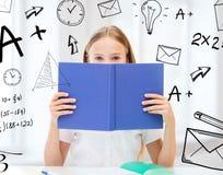 Κορίτσι που μελετά και που διαβάζει το βιβλίο στο σχολείο Στοκ Φωτογραφία