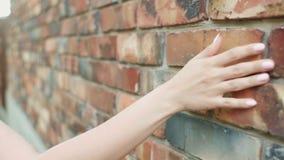 Κορίτσι που οδηγεί το χέρι της κατά μήκος ενός τούβλινου τοίχου, μια νέα γυναίκα που περπατά στην οδό, μια ρομαντική διάθεση, αφή απόθεμα βίντεο