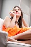 Κορίτσι που δοκιμάζει ένα μπισκότο στον καναπέ της Στοκ εικόνα με δικαίωμα ελεύθερης χρήσης