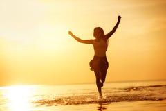 Κορίτσι που οργανώνεται ευτυχές στη λίμνη ηλιοβασιλέματος στοκ φωτογραφία με δικαίωμα ελεύθερης χρήσης