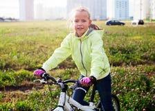 Κορίτσι που οδηγά ένα ποδήλατο σε έναν πράσινο τομέα Στοκ Εικόνα