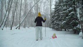 Κορίτσι που πέφτει στο χιόνι κάνοντας σκι με το mom απόθεμα βίντεο