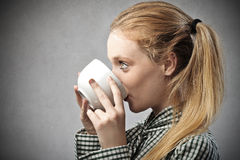 Κορίτσι που πίνει ένα φλυτζάνι του τσαγιού στοκ εικόνα