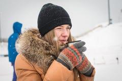 Κορίτσι που πίνει το καυτό τσάι στο χειμερινό δασικό πορτρέτο Μια νεολαία στα θερμά ενδύματα που κρατά το φλυτζάνι με το ποτό στο Στοκ Φωτογραφία