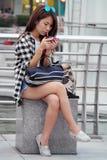 Κορίτσι που παίζει το κινητό τηλέφωνο στην οδό Στοκ Φωτογραφίες
