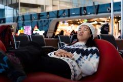 Κορίτσι που παίρνει ένα NAP περιμένοντας στον αερολιμένα στοκ εικόνες