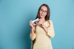 Κορίτσι που παίρνει τη φωτογραφία που χρησιμοποιεί το photocamera πέρα από το μπλε υπόβαθρο Στοκ φωτογραφία με δικαίωμα ελεύθερης χρήσης