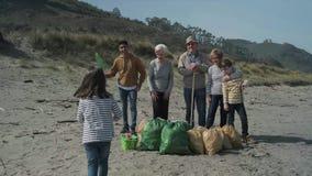 Κορίτσι που παίρνει τη φωτογραφία στην ομάδα εθελοντών μετά από να καθαρίσει την παραλία απόθεμα βίντεο