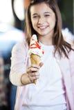 Κορίτσι που παρουσιάζει νόστιμο παγωτό με το σιρόπι φραουλών στοκ φωτογραφία