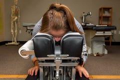 Κορίτσι που περιμένει σε έναν γέρνοντας Chiropractic πίνακα στο στομάχι της Ther στοκ φωτογραφία με δικαίωμα ελεύθερης χρήσης