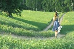 Κορίτσι που περπατά εμπρός στον τομέα Στοκ Φωτογραφία