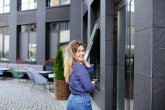 Κορίτσι που περπατά και που κρατά το smartphone στην πόλη Στοκ εικόνα με δικαίωμα ελεύθερης χρήσης