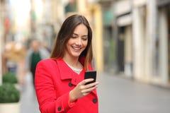Κορίτσι που περπατά και που στο έξυπνο τηλέφωνο στην οδό στο κόκκινο Στοκ εικόνα με δικαίωμα ελεύθερης χρήσης