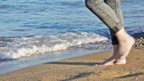 Κορίτσι που περπατά κατά μήκος μιας αμμώδους παραλίας φιλμ μικρού μήκους