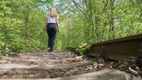 Κορίτσι που περπατά κατά μήκος των παλαιών ραγών απόθεμα βίντεο