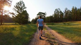 Κορίτσι που περπατά σε μια εθνική οδό στο ηλιοβασίλεμα E απόθεμα βίντεο