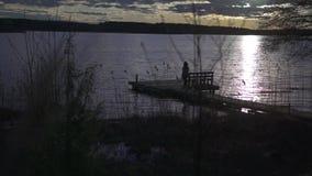 Κορίτσι που περπατά στην ξύλινη γέφυρα με τον πάγκο ε από την πλευρά μιας λίμνης στο ηλιοβασίλεμα απόθεμα βίντεο