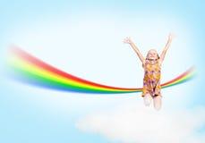 Κορίτσι που πηδά στα σύννεφα και ένα ουράνιο τόξο στοκ εικόνες