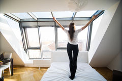Κορίτσι που πηδά και που έχει τη διασκέδαση στο κρεβάτι στοκ φωτογραφία
