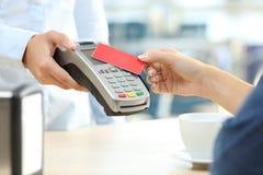 Κορίτσι που πληρώνει με έναν ανέπαφο αναγνώστη πιστωτικών καρτών σε έναν φραγμό Στοκ φωτογραφίες με δικαίωμα ελεύθερης χρήσης