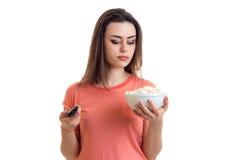 Κορίτσι που προσέχει μια TV και που κρατά ένα πιάτο με pop-corn Στοκ Φωτογραφία