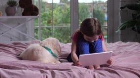 Κορίτσι που προσέχει τα αστεία κινούμενα σχέδια με το σκυλί κατοικίδιων ζώων στο εσωτερικό απόθεμα βίντεο