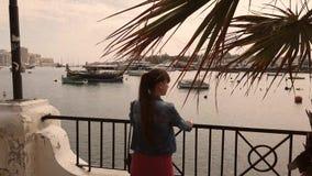 Κορίτσι που προσέχει τα σκάφη στο ηλιοβασίλεμα απόθεμα βίντεο