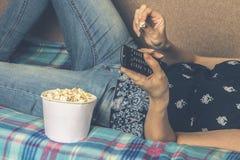 Κορίτσι που προσέχει τη TV με popcorn στο σπίτι στο καθιστικό Η έννοια της τεμπελιάς στοκ εικόνες