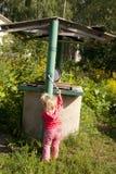 Κορίτσι που προσπαθεί να πάρει το νερό από τον παλαιό καλά Στοκ φωτογραφία με δικαίωμα ελεύθερης χρήσης