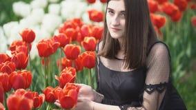 Κορίτσι που ρουθουνίζει τις κόκκινες τουλίπες απόθεμα βίντεο
