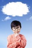 Κορίτσι που σκέφτεται κάτω από το άσπρο σύννεφο στοκ εικόνες