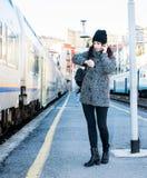 Κορίτσι που στέκεται δίπλα σε ένα τραίνο, που εξετάζει το ρολόι της και που μιλά στο τηλέφωνο στοκ εικόνα με δικαίωμα ελεύθερης χρήσης