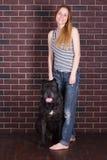 Κορίτσι που στέκεται κοντά στον τοίχο και που αγκαλιάζει έναν μεγάλο κάλαμο Corso σκυλιών Στοκ φωτογραφία με δικαίωμα ελεύθερης χρήσης