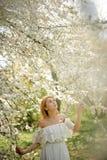 Κορίτσι που στέκεται μεταξύ των κλάδων του όμορφου άσπρου δέντρου και lookin επάνω στοκ εικόνες