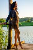 κορίτσι που στέκεται σε μια ξύλινη αποβάθρα Στοκ Φωτογραφία