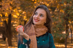 Κορίτσι που στέκεται στην οδό με τη Apple στο χέρι και τα χαμόγελά του Στοκ Εικόνα