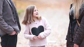Κορίτσι που στέκεται στο πάρκο και που μιλά με τους γονείς φιλμ μικρού μήκους