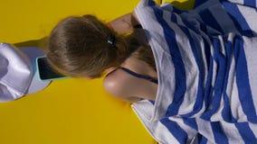 Κορίτσι που στηρίζεται στο μόνιππο longue και που φαίνεται κινητό τηλέφωνο κατά τη τοπ άποψη θερινής ημέρας απόθεμα βίντεο
