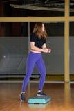 Κορίτσι που συμμετέχεται φίλαθλο στο βήμα στην πλατφόρμα για το βήμα στη γυμναστική Στοκ Φωτογραφίες