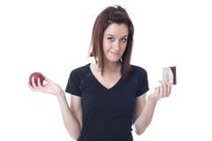 Κορίτσι που σχίζεται μεταξύ της κατανάλωσης ενός μήλου ή της κατανάλωσης της σοκολάτας Στοκ Εικόνες
