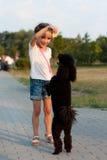 Κορίτσι που ταΐζει μαύρο poodle Στοκ φωτογραφία με δικαίωμα ελεύθερης χρήσης