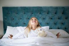 Κορίτσι που τεντώνει τα όπλα της ξυπνώντας στην κρεβατοκάμαρα Στοκ Φωτογραφίες