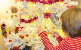 Κορίτσι που τοποθετεί τις διακοσμήσεις διακοσμήσεων Χριστουγέννων στοκ εικόνα με δικαίωμα ελεύθερης χρήσης