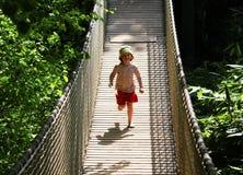Κορίτσι που τρέχει πέρα από τη γέφυρα στοκ εικόνα