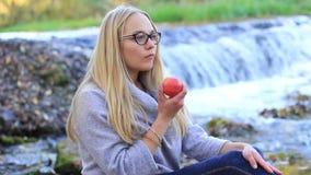 Κορίτσι που τρώει ένα μήλο κοντά σε έναν καταρράκτη απόθεμα βίντεο