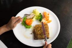 Κορίτσι που τρώει την μπριζόλα χοιρινού κρέατος με το μαχαίρι και το δίκρανο στοκ εικόνες