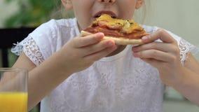 Κορίτσι που τρώει την πολυδιατηρημένη τσιγαρισμένη πίτσα, ανθυγειινό άχρηστο φαγητό, κίνδυνος παχυσαρκίας απόθεμα βίντεο